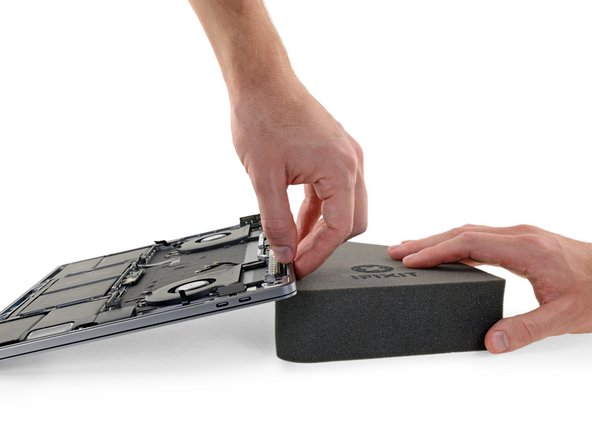 To control the flow of adhesive remover, raise the back edge (hinge side) of your MacBook Pro a few inches using a book or foam block.