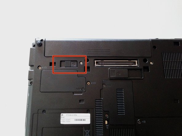 Flip laptop over and locate the battery release button