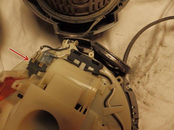 Auf der Kabeltrommel befindet sich der Schalter. Das Kabel ist mit einer Flachsteckverbindung verbunden, die durch eine feine Nase gesichert ist, damit sie sich nicht durch Vibration löst. Wenn Du mit einem feinen Schraubenzieher auf die Nase drückst, lässt sich die Verbindung ohne größere Kräfte lösen. Löse das schwarze Kabel.