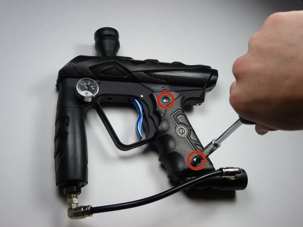 Remove the four 8mm screws on each side of the gun's grip using a Phillips #2 screwdriver.