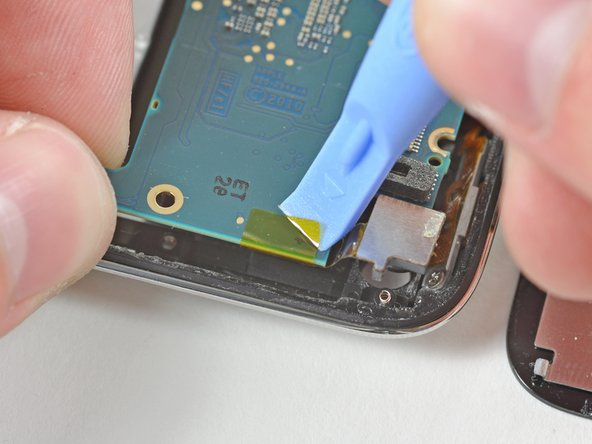 Use an iPod opening tool to peel the edge of the yellow kapton tape that covers the rear-facing camera and the logic board.