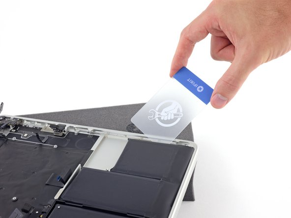 Gently slide a plastic card or other thin pry tool under the adhered component.