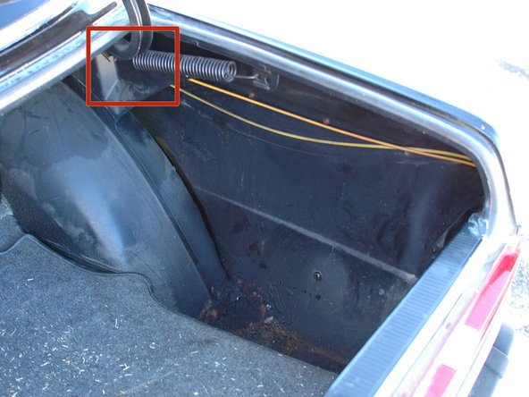 The gas door lock actuator is accessible in the trunk of the car. Open the trunk, and then pull up the plastic paneling that covers the bottom of the trunk well on the passenger side of the vehicle. The picture shows the well after the panel has been removed.