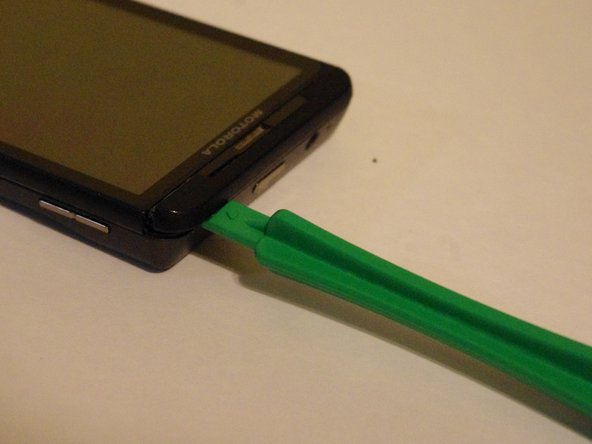 Now do the same to the top of the phone with your opening tool as shown to remove the other plastic piece covering the top of the phone.
