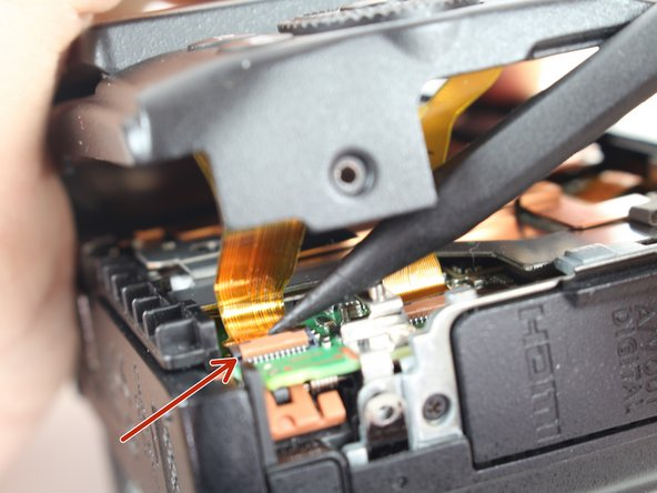 Use a plastic spudger to gently release the locking tab holding the ribbon cable, closest to the edge of the camera, in place.