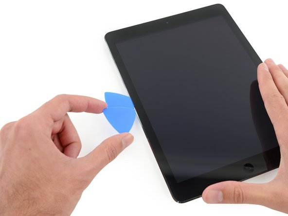 Place a second opening pick alongside the first and slide the pick down along the edge of the iPad, releasing the adhesive as you go.
