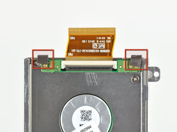 Carefully peel up the two foam bumpers from the ends stuck to the bottom of the hard drive.
