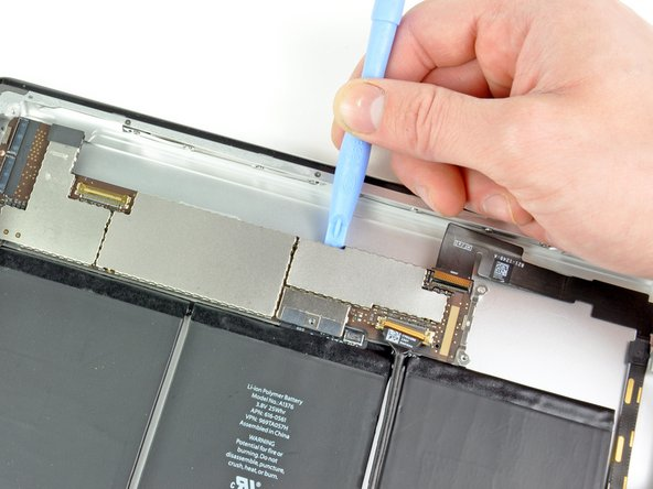 Use the edge of a plastic opening tool to gently pry the logic board up from the adhesive securing it to the rear case.