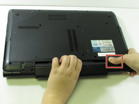 Hold down the tab on the right side, then begin sliding the battery out.