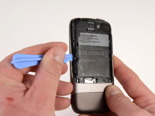 Using the plastic opening tool, pry up the battery housing upwards.