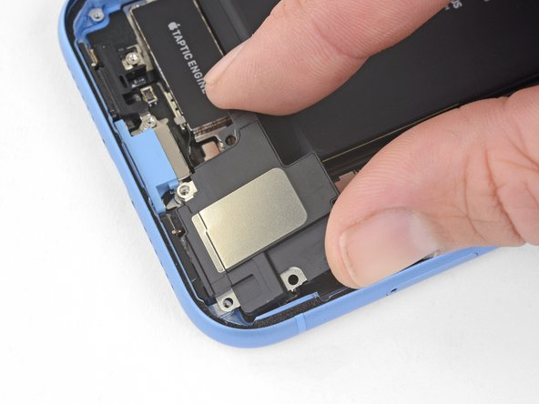 Hold the speaker by its side edges and rock it side-to-side, separating the adhesive securing it to the bottom edge of the iPhone.
