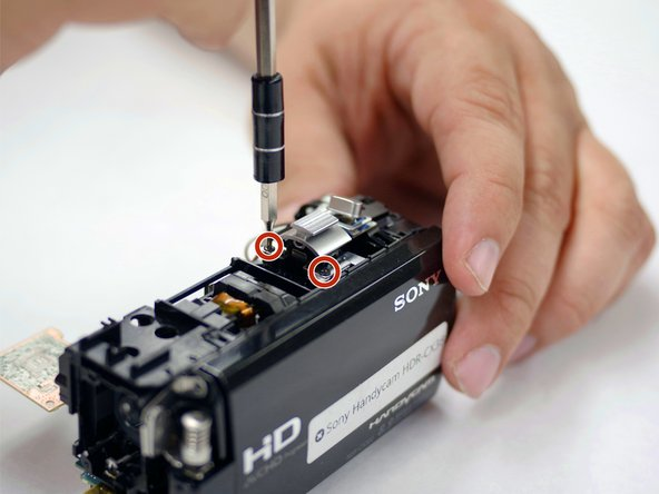 With the back of the LCD screen facing toward you, remove the two 5.5 mm Phillips #00 screws from the zoom button.