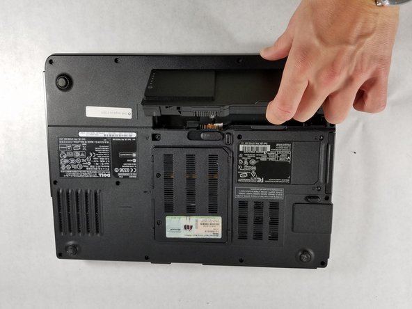 "Locate the ""lip"" on the laptop to lift the battery outside of the compartment."