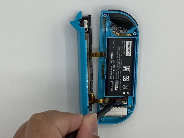 Gently pry the battery connector straight up from its socket on the motherboard using a spudger. This will keep the Joy-Con from powering on during the repair.