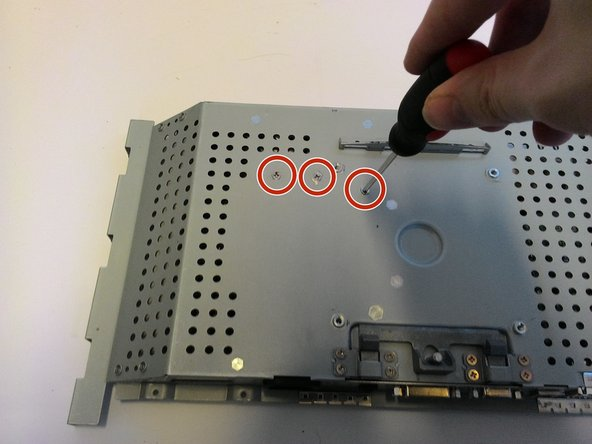 After all the capacitors are safely discharged, flip the housing over and remove the three indicated screws from the back.
