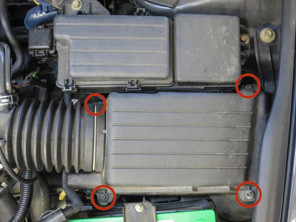 Unscrew the four bolts in the corners of the Air Filter Housing. This loosens the top of the housing from the bottom of the housing.