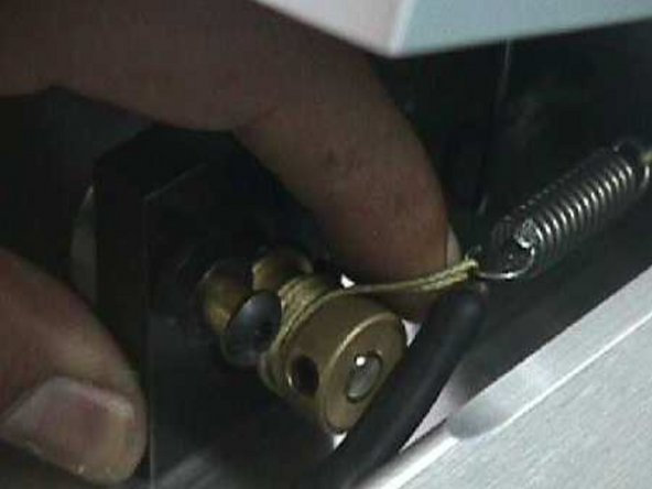 From the side of the open pedal, hold spring in place while carefully attaching the long cord's loop to remaining end of the spring.