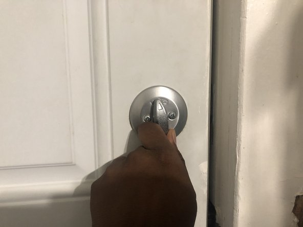 Turn the lock clockwise until two screws are visible.