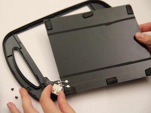 By holding onto both the USB port and the solar panel, remove both the circuit board and solar panel from the casing.