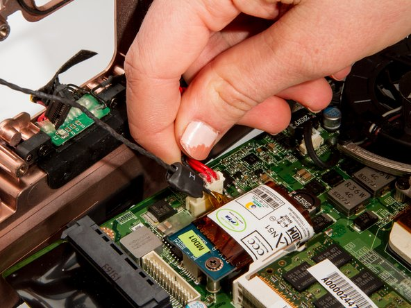 Remove auxiliary power cable attached to the blue board at the back of the laptop.