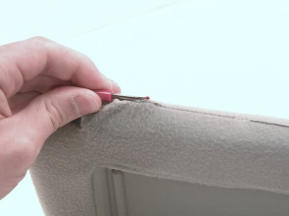 Tear open the seam surrounding the hole that the swing arm inserts into with a  seam ripper.