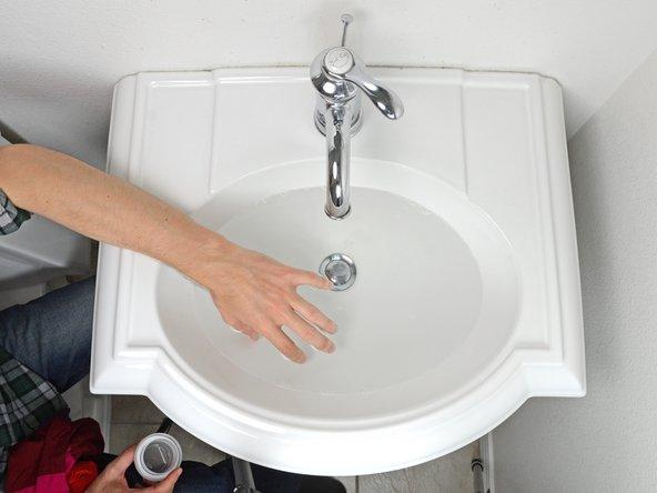 Das Waschmittel mit der Hand im Wasser verteilen.