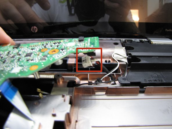 Underneath the far right side of the motherboard, you'll see another slide connector - pull it to the right