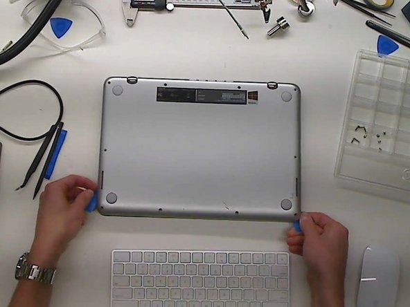 Use a plastic pry tool to get in-between the bottom cover and the lower case assembly.