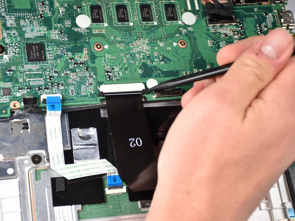 Slide back both sides of the locking mechanism of the touchpad using the narrow end of the spudger.