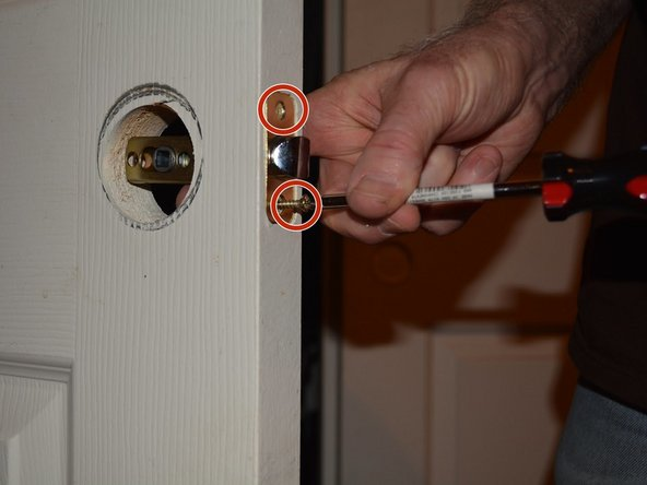Unscrew the two short screws on the latch face plate.