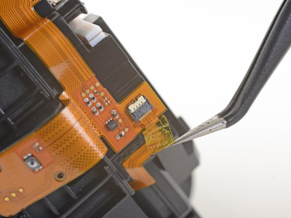 Use a pair of tweezers to peel back the plastic covering the eyepiece midframe cable socket.