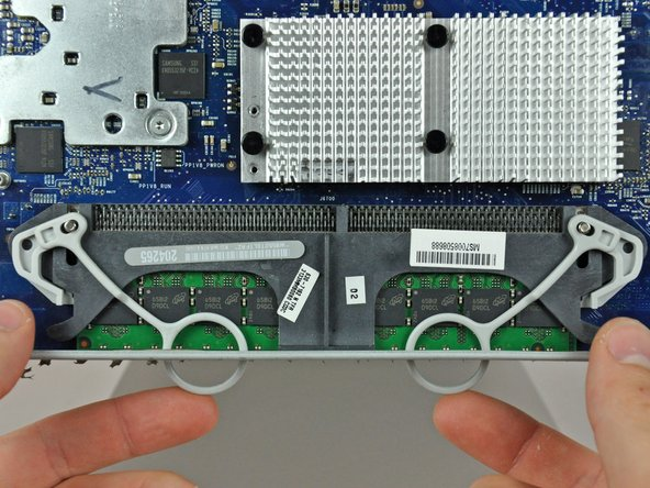 Tuck the RAM arms into the iMac so they rest on the perforated metal grille along its lower edge.