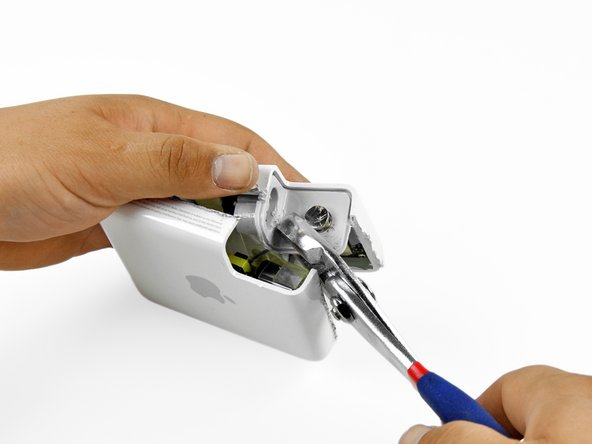 Remove the grey power inlet from the case half it is still attached to. Use a pair of pliers to rock the power inlet back and forth until it breaks free from the glue.