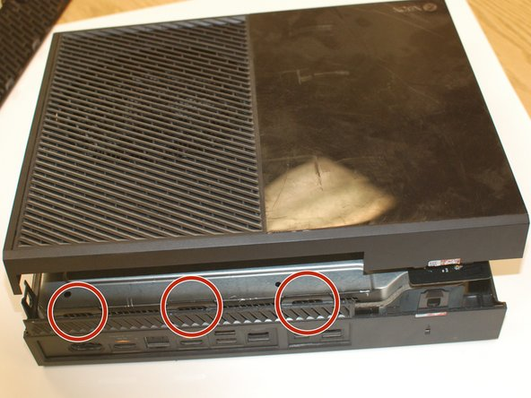 Now on the backside use a flat screwdriver to pry the back clips straight off to separate the lid. It helps to center the screwdriver in the middle of each clip.