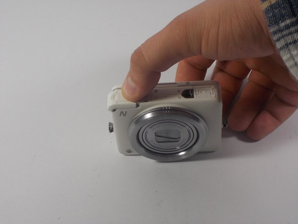 Place finger on the textured portion of battery housing cover and slide cover in the direction indicated.