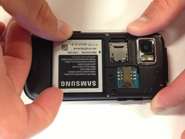 Place your finger in either of the bottom corner of the battery slot and lift to remove the battery.