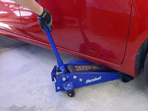 Pump the jack handle down and back up repeatedly to begin raising your vehicle.