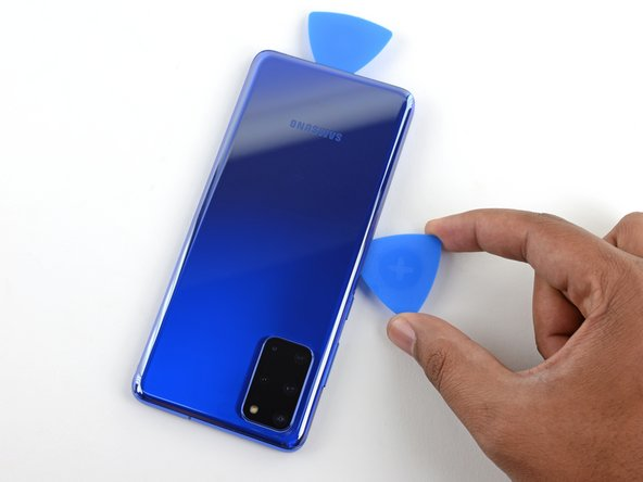 Slide the pick all along the left edge of the phone to separate the back cover's adhesive.