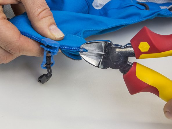 Remove the zip stop at the end of the zip by prying it open with a wire cutter and pulling it away.