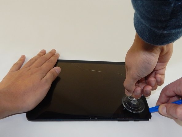 Insert the plastic opening tool into the gap on the side of the tablet, near a corner where you want to start removing the screen.