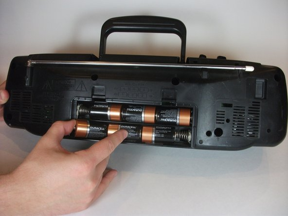 Push the batteries against the spring and pull out using your finger to remove them.