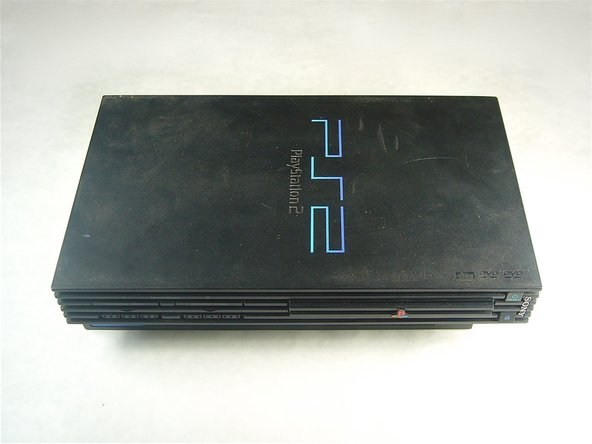 Flip the PlayStation 2 over so it lays with the bottom of the device facing upwards.