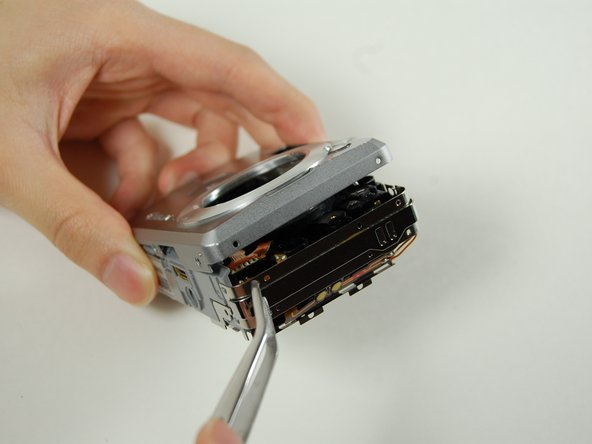 Use your tweezers to hold the camera secure, while you pull the front cover off of the camera.