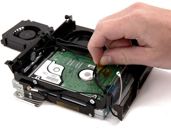 Peel up the yellow tape securing the speaker and fan cables to the bottom of the hard drive.