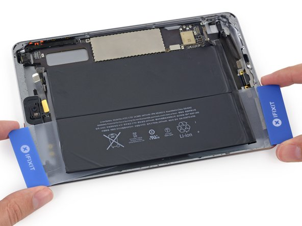 Grasp both cards and slowly pull the case-side cell of the battery up about two inches from the rear case.