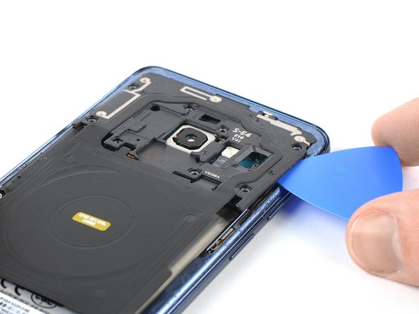 Insert an opening pick under the right side of the plastic cover containing the NFC antenna and charging coil.
