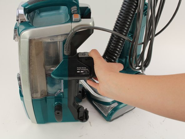 Press down on the hose release button and pull away from the vacuum.