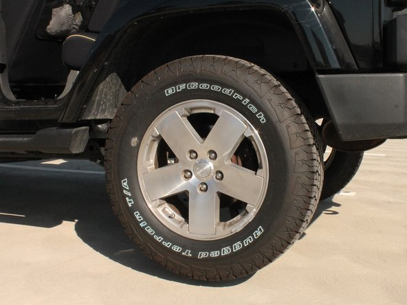 (Picture 2, view from rear bumper) Open the trunk and remove the trunk's carpeting by simply reaching underneath and pulling up.  The tools needed for changing a spare tire are located underneath the carpeting.  Take out the following tools: