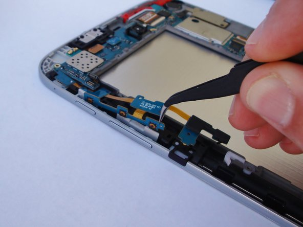 Using tweezers, pull the part of the cable that is located behind the volume buttons out of the slot.