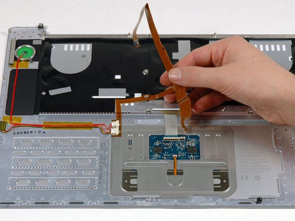 Carefully peel up the orange ribbon cable which carries the power and sleep signals, removing tape as necessary